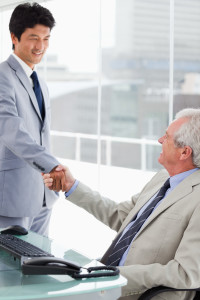 Portrait of a smiling employee shaking the hand of his manager in an office